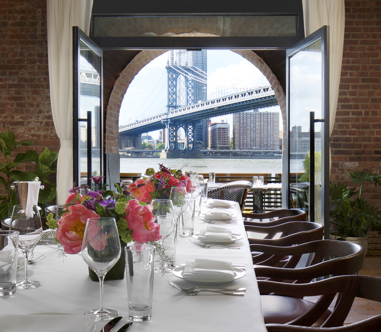 A dining table with a view of Brooklyn Bridge