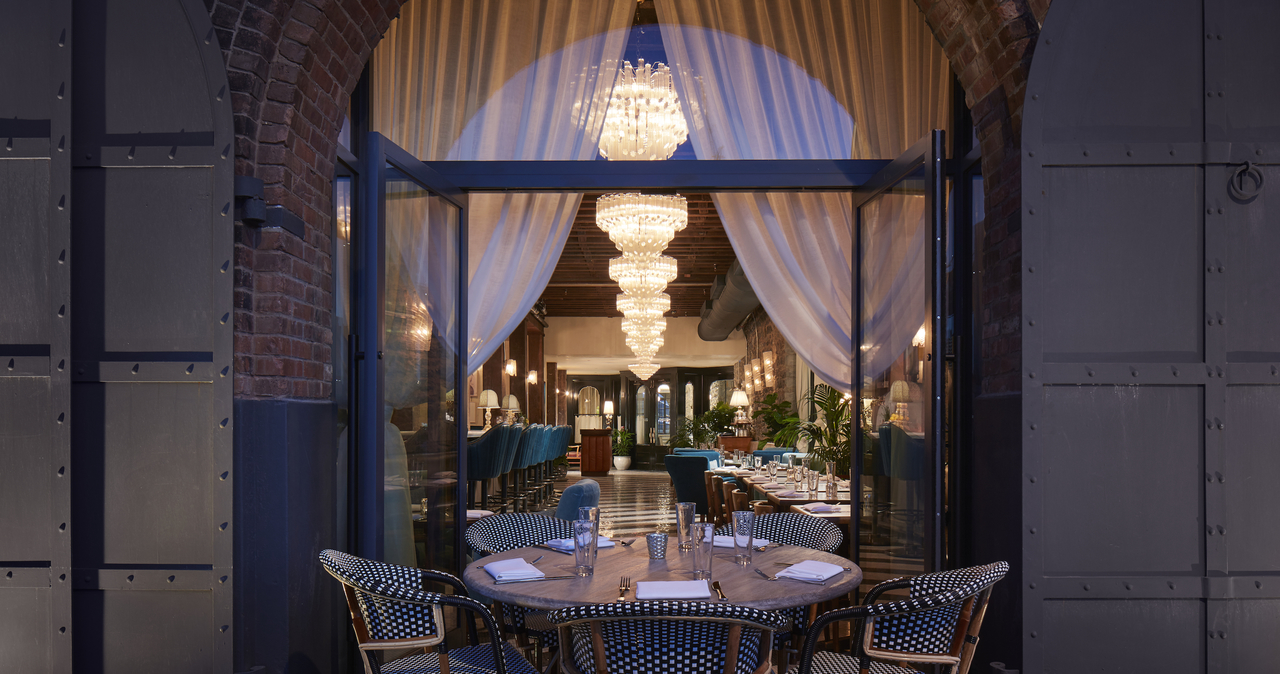 A view of the restaurant through French doors at night